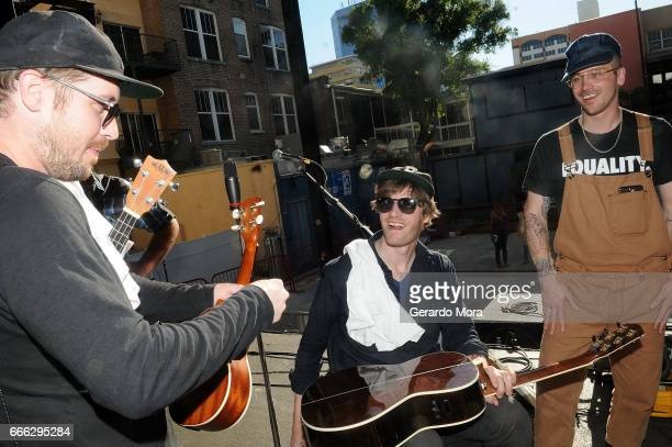 Zachary Scott Carothers Eric Howk and John Baldwin Gourley of the Portugal The Man sign autographs for the Noisemakers kids after the soundcheck at...