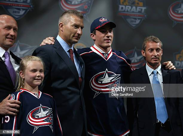 Zachary Werenski poses with team personnel after being selected 8th by the the Columbus Blue Jackets during Round One of the 2015 NHL Draft at BBT...