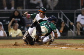 Zack Collins of the Miami Hurricanes scores past the attempted tag by Forrest Johnson of the Notre Dame Fighting Irish on April 21 2014 at Alex...