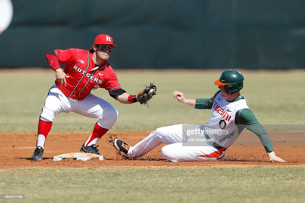 Zack Collins of the Miami Hurricanes steals second base ahead of the tag by John Jennings of the Rutgers Scarlet Knights on February 15 2015 at Alex...