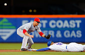 Zack Cozart of the Cincinnati Reds can't come up with the ball as Alejandro De Aza of the New York Mets tags up from first base during the first...