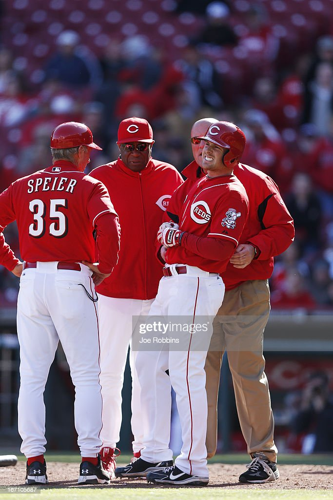 <a gi-track='captionPersonalityLinkClicked' href=/galleries/search?phrase=Zack+Cozart&family=editorial&specificpeople=6889199 ng-click='$event.stopPropagation()'>Zack Cozart</a> #2 of the Cincinnati Reds gets attention from manager <a gi-track='captionPersonalityLinkClicked' href=/galleries/search?phrase=Dusty+Baker&family=editorial&specificpeople=202908 ng-click='$event.stopPropagation()'>Dusty Baker</a> and third base coach Chris Speier after being hit by the ball while trying to bunt against the Miami Marlins at Great American Ball Park on April 20, 2013 in Cincinnati, Ohio. The Reds won 3-2 in 13 innings.