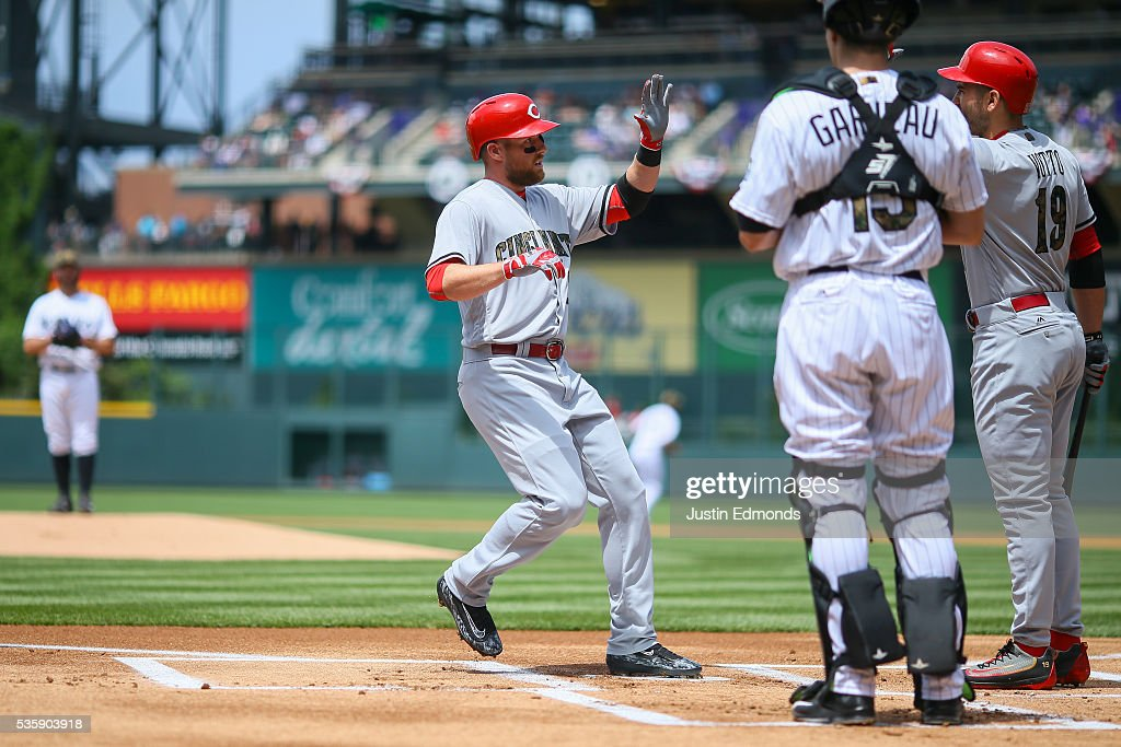 <a gi-track='captionPersonalityLinkClicked' href=/galleries/search?phrase=Zack+Cozart&family=editorial&specificpeople=6889199 ng-click='$event.stopPropagation()'>Zack Cozart</a> #2 of the Cincinnati Reds is congratulated at home plate by <a gi-track='captionPersonalityLinkClicked' href=/galleries/search?phrase=Joey+Votto&family=editorial&specificpeople=759319 ng-click='$event.stopPropagation()'>Joey Votto</a> #19 after hitting a solo home run on the first pitch of the game as Dustin Garneau #13 of the Colorado Rockies looks on in the first inning at Coors Field on May 30, 2016 in Denver, Colorado.
