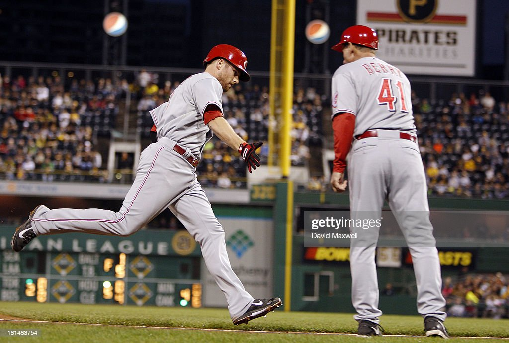 <a gi-track='captionPersonalityLinkClicked' href=/galleries/search?phrase=Zack+Cozart&family=editorial&specificpeople=6889199 ng-click='$event.stopPropagation()'>Zack Cozart</a> #2 of the Cincinnati Reds is congratulated by Third Base Coach Mark Berry #41 as he rounds the bases after hitting a solo home run during the second inning of their game against the Pittsburgh Pirates on September 21, 2013 at PNC Park in Pittsburgh Pennsylvania.