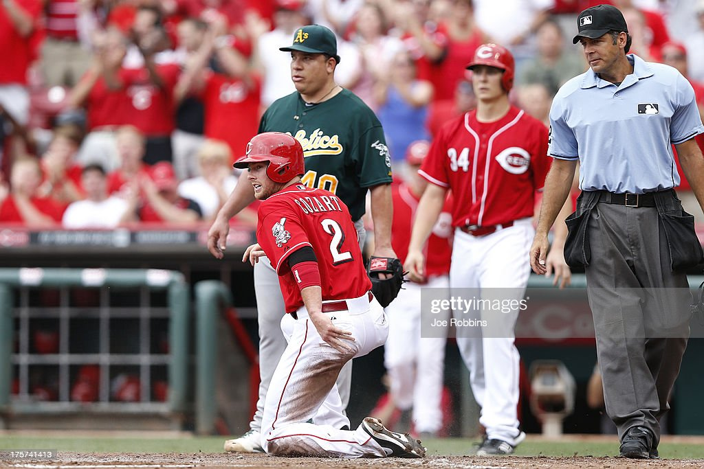 <a gi-track='captionPersonalityLinkClicked' href=/galleries/search?phrase=Zack+Cozart&family=editorial&specificpeople=6889199 ng-click='$event.stopPropagation()'>Zack Cozart</a> #2 of the Cincinnati Reds kneels after sliding home with a run after a double by Corky Miller in the third inning of the game against the Oakland Athletics at Great American Ball Park on August 7, 2013 in Cincinnati, Ohio.