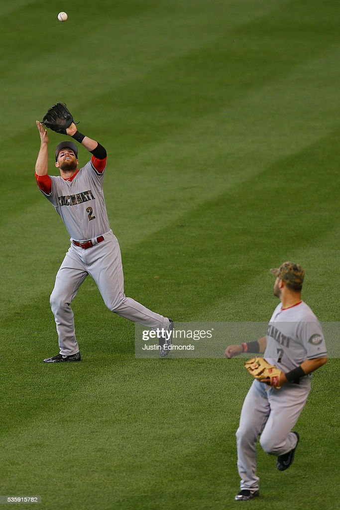 <a gi-track='captionPersonalityLinkClicked' href=/galleries/search?phrase=Zack+Cozart&family=editorial&specificpeople=6889199 ng-click='$event.stopPropagation()'>Zack Cozart</a> #2 of the Cincinnati Reds makes a catch for the third out of the fourth inning as <a gi-track='captionPersonalityLinkClicked' href=/galleries/search?phrase=Eugenio+Suarez&family=editorial&specificpeople=10488763 ng-click='$event.stopPropagation()'>Eugenio Suarez</a> #7 looks on against the Colorado Rockies at Coors Field on May 30, 2016 in Denver, Colorado.