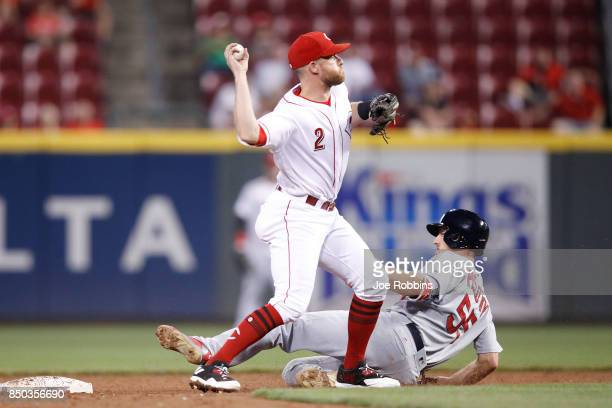 Zack Cozart of the Cincinnati Reds throws to first after getting a force out at second base ahead of the sliding Stephen Piscotty of the St Louis...