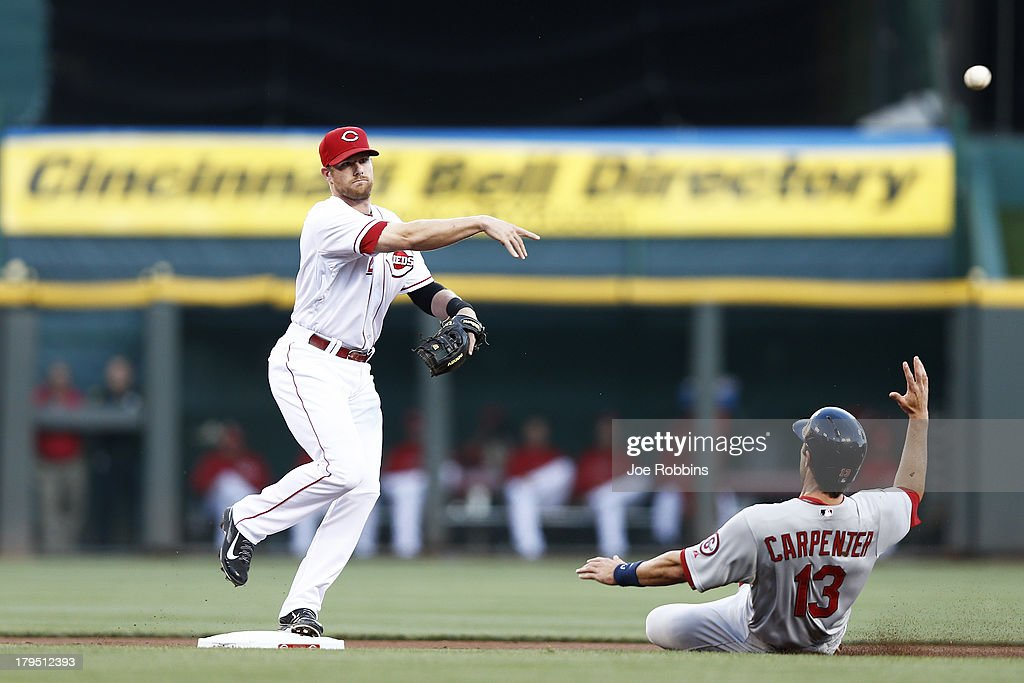 <a gi-track='captionPersonalityLinkClicked' href=/galleries/search?phrase=Zack+Cozart&family=editorial&specificpeople=6889199 ng-click='$event.stopPropagation()'>Zack Cozart</a> #2 of the Cincinnati Reds turns a double play against Matt Carpenter #13 of the St. Louis Cardinals in the first inning of the game at Great American Ball Park on September 4, 2013 in Cincinnati, Ohio.