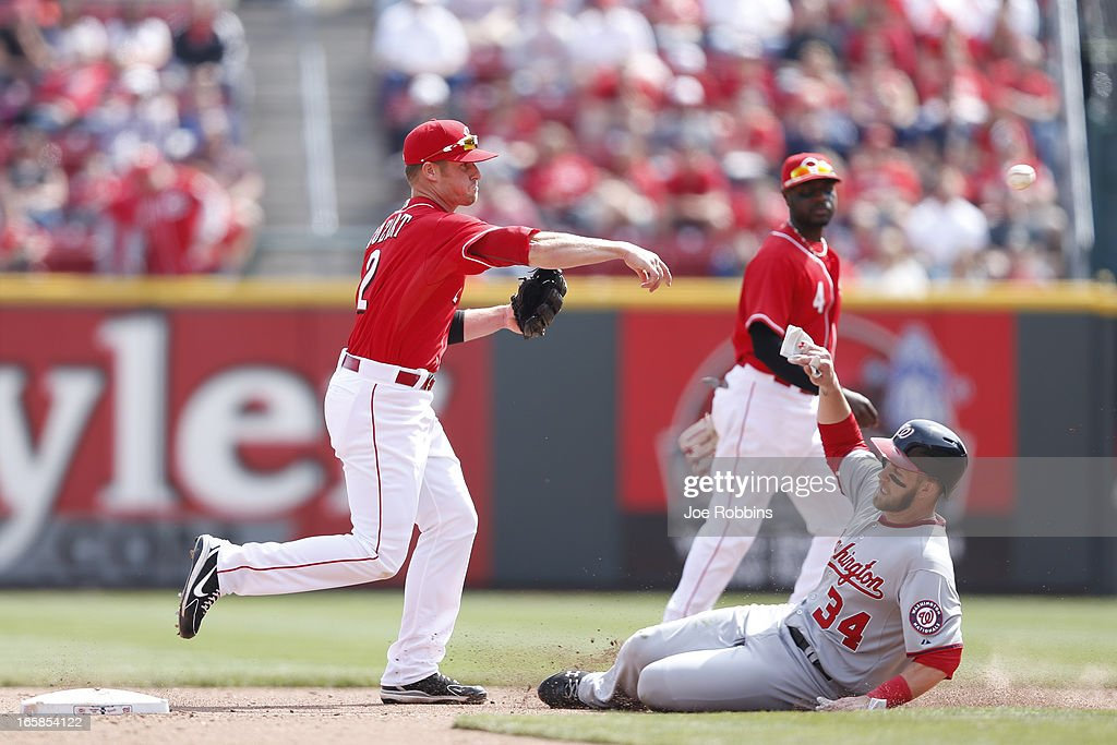 <a gi-track='captionPersonalityLinkClicked' href=/galleries/search?phrase=Zack+Cozart&family=editorial&specificpeople=6889199 ng-click='$event.stopPropagation()'>Zack Cozart</a> #2 of the Cincinnati Reds turns a double play over <a gi-track='captionPersonalityLinkClicked' href=/galleries/search?phrase=Bryce+Harper&family=editorial&specificpeople=5926486 ng-click='$event.stopPropagation()'>Bryce Harper</a> #34 of the Washington Nationals during the game at Great American Ball Park on April 6, 2013 in Cincinnati, Ohio. The Nationals won 7-6 in 11 innings.