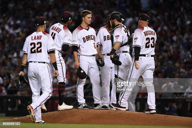 Zack Greinke of the Arizona Diamondbacks talks with team mates Ketel Marte and Jeff Mathis during the third inning of the National League Divisional...