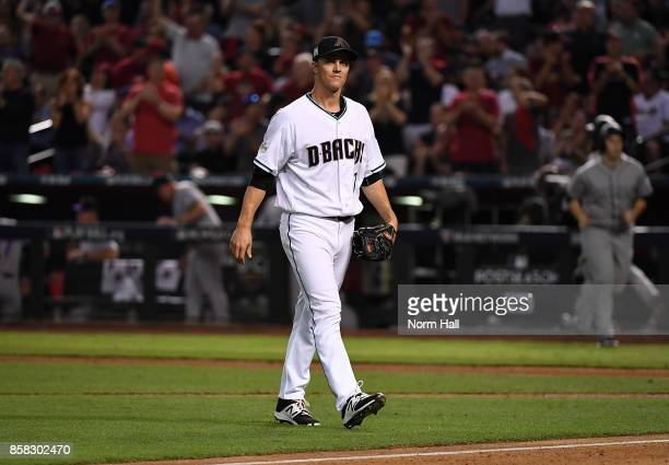 Zack Greinke of the Arizona Diamondbacks walks back to his dugout after being romoved from the game during the fourth inning against the Colorado...