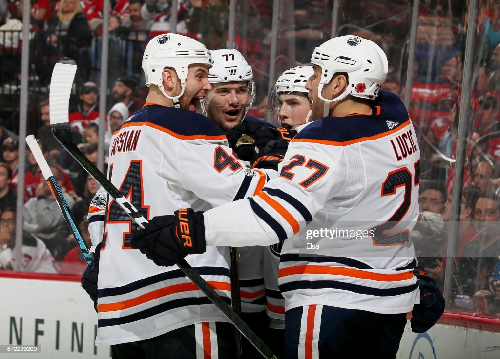 Zack Kassian #44 and Oscar Klefbom #77 of the Edmonton Oilers congratulate teammate Milan Lucic #27 after he scored in the third period against the New Jersey Devils on November 9, 2017 at Prudential Center in Newark, New Jersey.