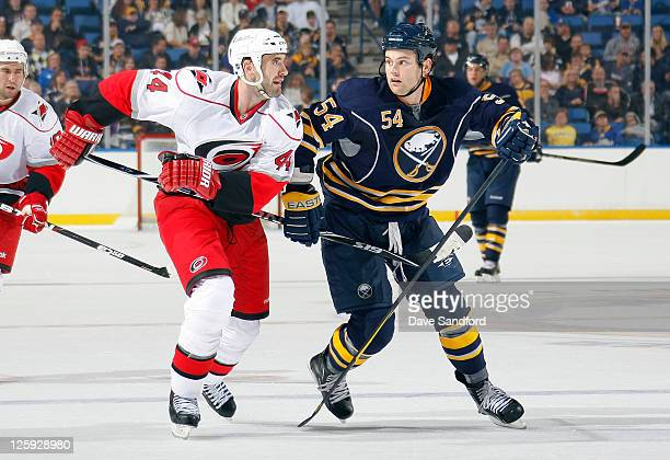 Zack Kassian of the Buffalo Sabres battles for position against Jay Harrison of the Carolina Hurricanes during their preseason NHL game at First...