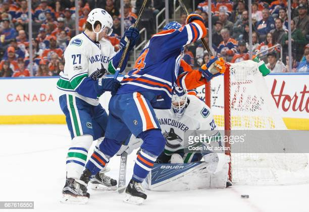 Zack Kassian of the Edmonton Oilers is shoved into goalie Richard Bachman by Ben Hutton of the Vancouver Canucks on April 9 2017 at Rogers Place in...