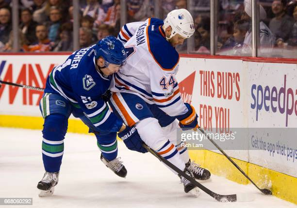 Zack Kassian of the Edmonton Oilers tires to gain control of the puck while being defended against by Troy Stecher of the Vancouver Canucks in NHL...