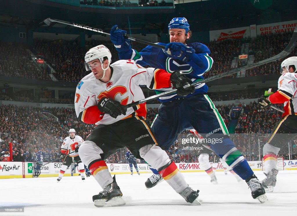 <a gi-track='captionPersonalityLinkClicked' href=/galleries/search?phrase=Zack+Kassian&family=editorial&specificpeople=4604939 ng-click='$event.stopPropagation()'>Zack Kassian</a> #9 of the Vancouver Canucks checks <a gi-track='captionPersonalityLinkClicked' href=/galleries/search?phrase=TJ+Brodie&family=editorial&specificpeople=7220398 ng-click='$event.stopPropagation()'>TJ Brodie</a> #7 of the Calgary Flames during their NHL game at Rogers Arena April 6, 2013 in Vancouver, British Columbia, Canada. Vancouver won 5-2