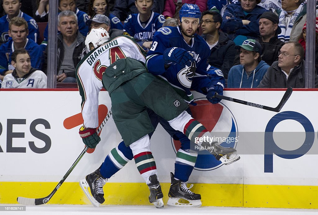 <a gi-track='captionPersonalityLinkClicked' href=/galleries/search?phrase=Zack+Kassian&family=editorial&specificpeople=4604939 ng-click='$event.stopPropagation()'>Zack Kassian</a> #9 of the Vancouver Canucks is hit by <a gi-track='captionPersonalityLinkClicked' href=/galleries/search?phrase=Mikael+Granlund&family=editorial&specificpeople=5649678 ng-click='$event.stopPropagation()'>Mikael Granlund</a> #64 of the Minnesota Wild along the side boards during the third period in NHL action on February 12, 2013 at Rogers Arena in Vancouver, British Columbia, Canada.
