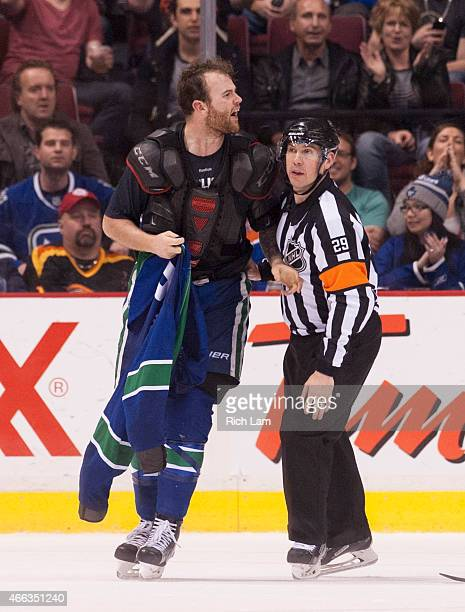 Zack Kassian of the Vancouver Canucks is led off the ice by referee Ian Walsh in NHL action on March 2015 at Rogers Arena in Vancouver British...