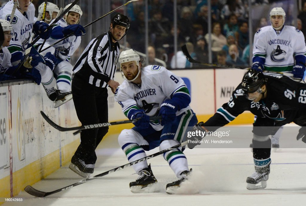 Zack Kassian #9 of the Vancouver Canucks passes the puck up ice past Michal Handzus #26 of the San Jose Sharks at HP Pavilion on January 27, 2013 in San Jose, California.