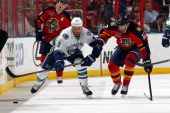 Zack Kassian of the Vancouver Canucks skates along the boards against Jimmy Hayes of the Florida Panthers at the BBT Center on March 16 2014 in...