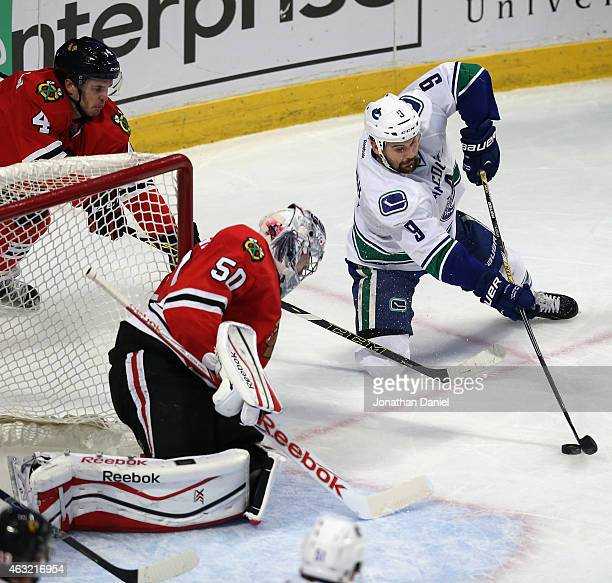 Zack Kassian of the Vancouver Canucks tires to get off a shot from one knee against Corey Crawford of the Chicago Blackhawks and Niklas Hjalmarsson...
