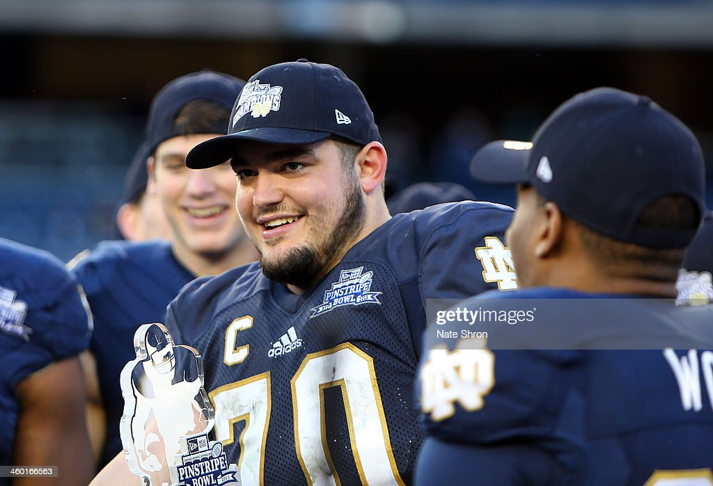 Zack Martin #70 of the Notre Dame Fighting Irish runs celebrates after being named MVP of the New Era Pinstripe Bowl after the team's win over the Rutgers Scarlet Knights during the New Era Pinstripe Bowl at Yankee Stadium on December 28, 2013 in the Bronx Borough of New York City.