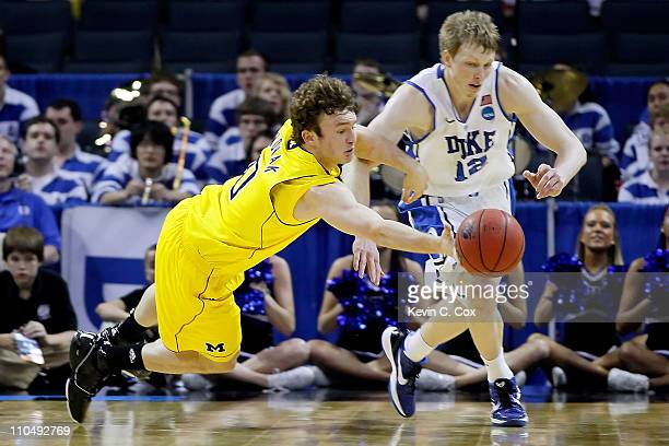 Zack Novak of the Michigan Wolverines dives for the ball alongside Kyle Singler of the Duke Blue Devils in the first half during the third round of...