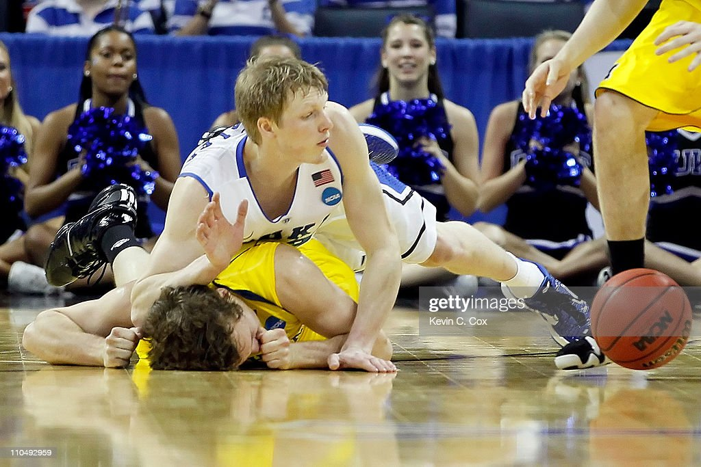 Zack Novak of the Michigan Wolverines is landed on after being jumped on by Kyle Singler of the Duke Blue Devils in the first half as they go for a...