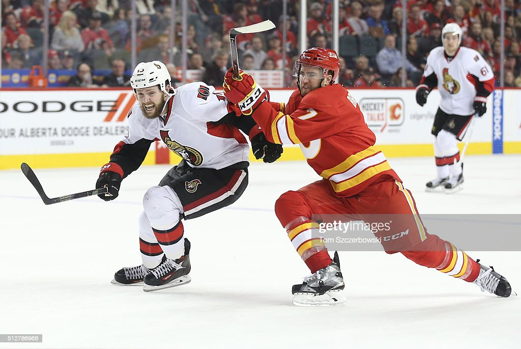 Zack Smith #15 of the Ottawa Senators and T.J. Brodie #7 of the Calgary Flames chase the puck during their NHL game at the Scotiabank Saddledome on February 27, 2016 in Calgary, Alberta, Canada.