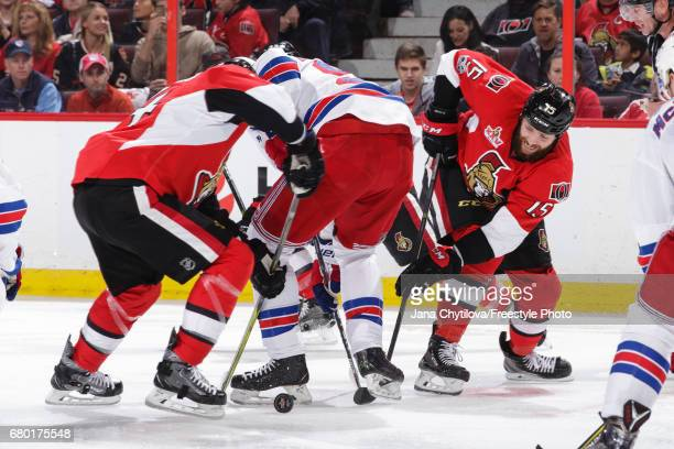 Zack Smith of the Ottawa Senators battles for the puck along with teammate Alexandre Burrows against Mika Zibanejad of the New York Rangers in Game...