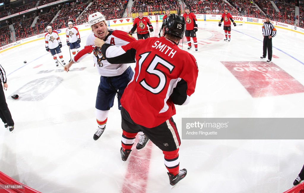 Zack Smith #15 of the Ottawa Senators fights with <a gi-track='captionPersonalityLinkClicked' href=/galleries/search?phrase=Erik+Gudbranson&family=editorial&specificpeople=5741800 ng-click='$event.stopPropagation()'>Erik Gudbranson</a> #44 of the Florida Panthers as teammates look on at Canadian Tire Centre on November 9, 2013 in Ottawa, Ontario, Canada.