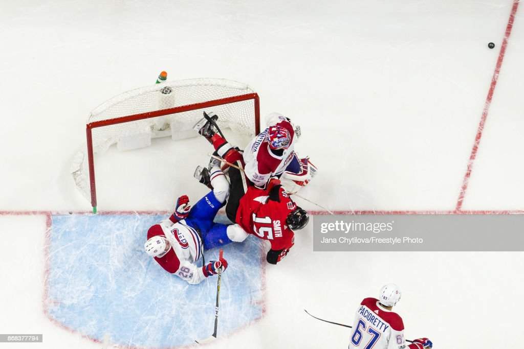 Zack Smith #15 of the Ottawa Senators gets hauled down by Jeff Petry #26 of the Montreal Canadiens causing them to crash into Al Montoya #35 of the Montreal Canadiens in the third periodat Canadian Tire Centre on October 30, 2017 in Ottawa, Ontario, Canada.
