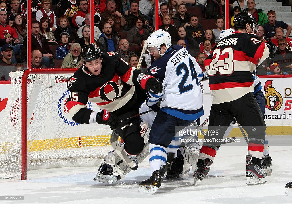 Zack Smith #15 of the Ottawa Senators goes flying as he battles for position in front of the net along with teammate Kaspars Daugavins #23 against Grant Clitsome #24 of the Winnipeg Jets during an NHL game at Scotiabank Place on February 9, 2013 in Ottawa, Ontario, Canada.