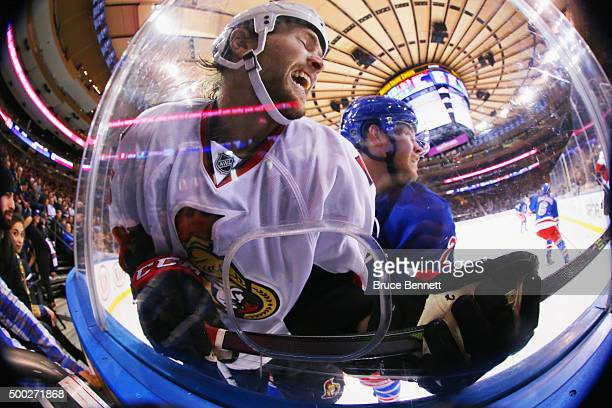 Zack Smith of the Ottawa Senators is checked into the boards by Oscar Lindberg of the New York Rangers during the first period at Madison Square...