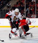 Zack Smith of the Ottawa Senators is tripped up by Martin Brodeur of the New Jersey Devils in the third period at the Prudential Center on December...