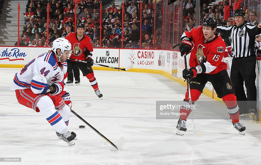 Zack Smith #15 of the Ottawa Senators passes the puck against <a gi-track='captionPersonalityLinkClicked' href=/galleries/search?phrase=Steve+Eminger&family=editorial&specificpeople=221303 ng-click='$event.stopPropagation()'>Steve Eminger</a> #44 of the New York Rangers on March 28, 2013 at Scotiabank Place in Ottawa, Ontario, Canada.