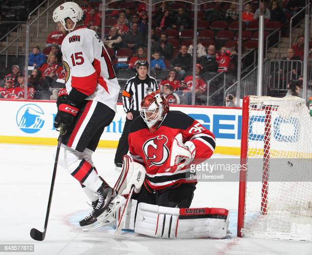 Zack Smith of the Ottawa Senators screens goalie Cory Schneider of the New Jersey Devils as a shot by Erik Karlsson of the Senators goes into the net...