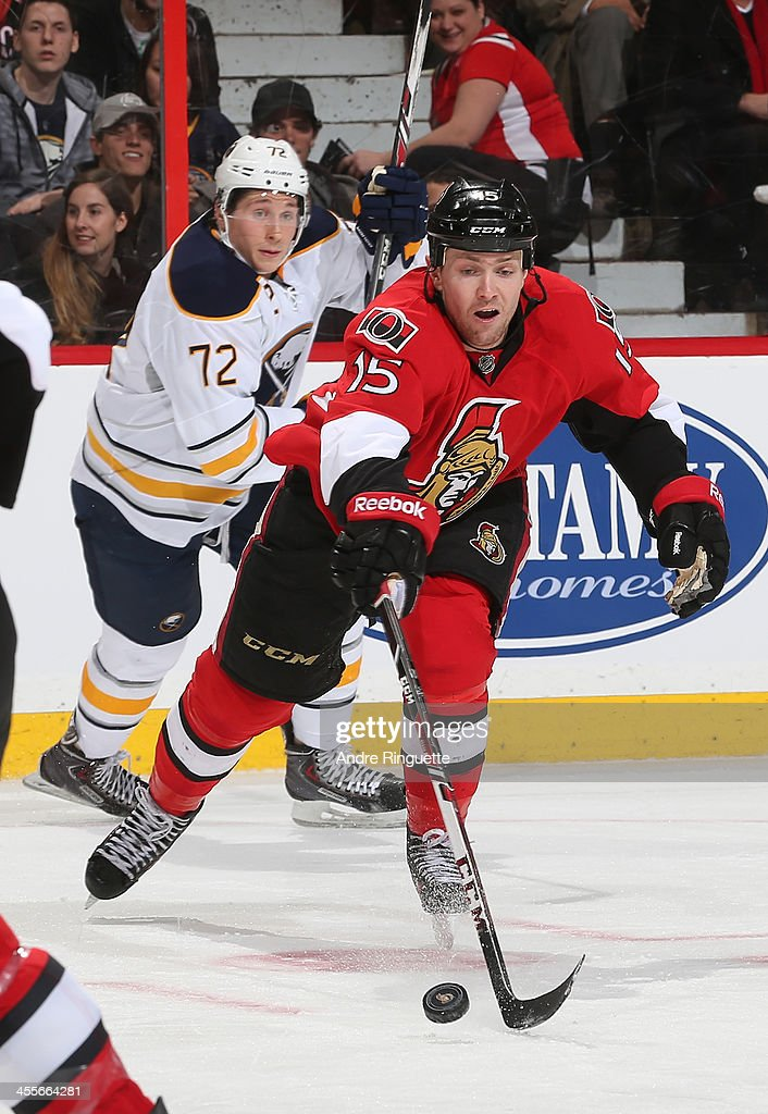 Zack Smith of the Ottawa Senators skates away from Luke Adam of the Buffalo Sabres with the puck at Canadian Tire Centre on December 12 2013 in...