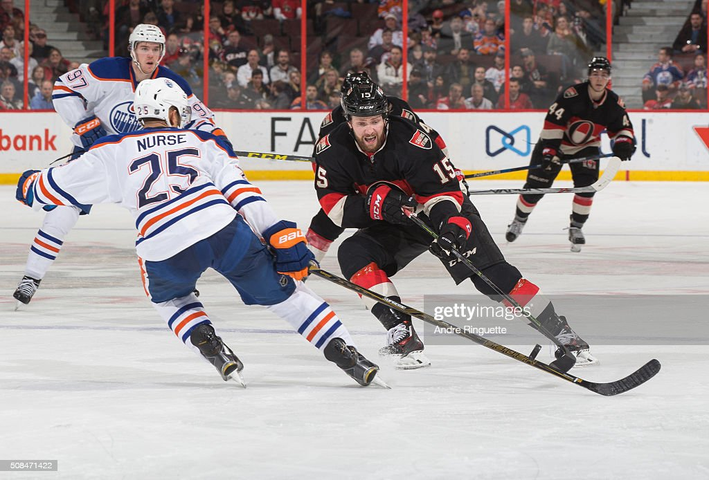 Zack Smith #15 of the Ottawa Senators stickhandles the puck against Darnell Nurse #25 of the Edmonton Oilers at Canadian Tire Centre on February 4, 2016 in Ottawa, Ontario, Canada.