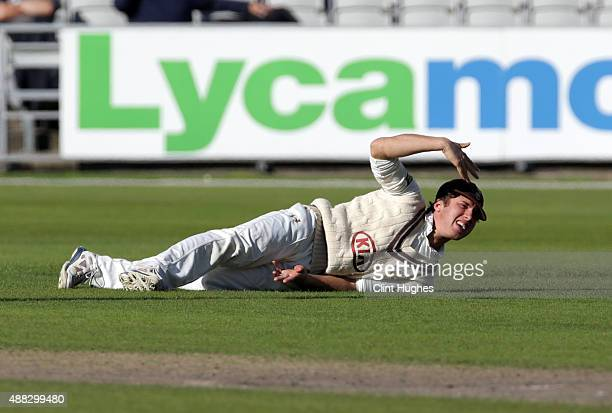 Zafar Ansari of Surrey waves for attention as he injures his hand fielding during day two of the LV County Championship Division Two match between...