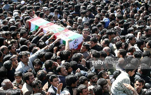 Iranian men carry a coffin during the funeral of 11 Revolutionary Guards who were killed two days ago when a boobytrapped car exploded in front of a...