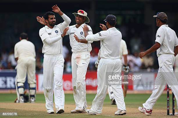 Zaheer Khan celebrates with India teammates VVS Laxman and Rahul Dravid after taking his fifth wicket of the innings and bowling Mike Hussey of...