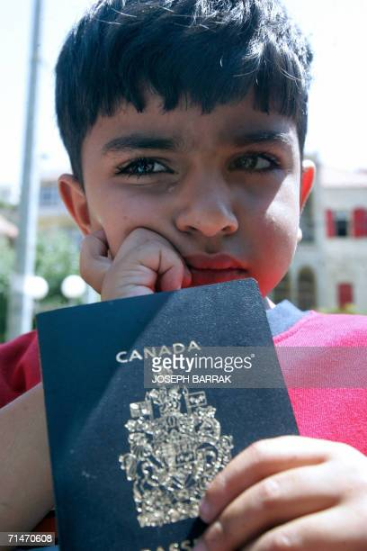 A LebaneseCanadian boy cries as he holds his Canadian passport in front of alQaderi hotel in Zahle city in the Bekaa valley as Canadian nationals get...