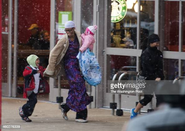 Zahrah Ghanim and her two children Jamil 4 and her 1 year old daughter Mariam rush inside the Target store as strong winds and flurries move through...