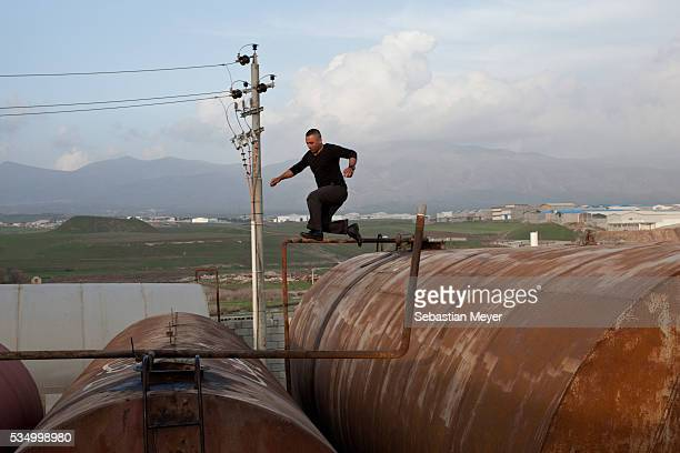 Zaidoon jumps between the storage drums in the refinery The family of Yezidis displaced from Sinjar live next to an oil refinery in the Kurdish...