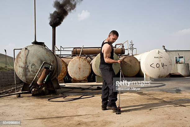 Zaidoon poses in front of an oil refinery with a piece of tension workout equipment Zaidoon is an amateur bodybuilder who was displaced from Sinjar...