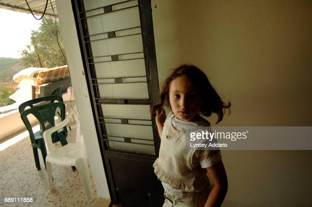 Zaineb Qasem turns away from the door scared as Israelis shoot machine gun fire towards their house on the edge of their village of Ait al Chab in...