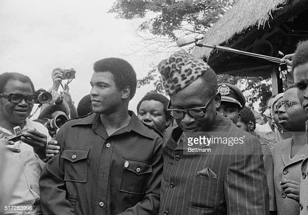 Zaire President Joseph Mobuto shows his elaborate walking stick to heavyweight challenger Muhammed Ali during a stroll around the gardens of the...