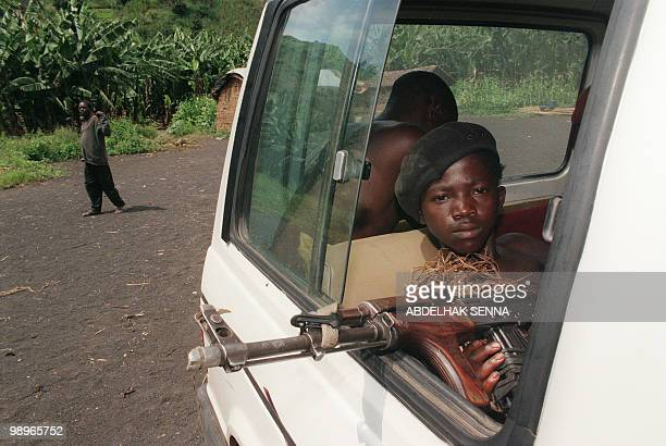 A Zairian MaiMai militia rebel child soldier pokes his AK47 Kalashnikov assault rifle out of a vehicle 01 December 1996 as he and others head for...