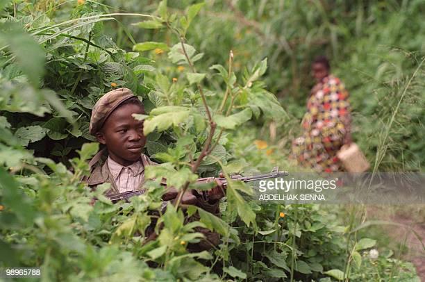 A Zairian Tutsi rebel child soldier holding his AK47 Kalashnikov assault rifle 28 November 1996 stands guard in foliage near Goma while a refugee...